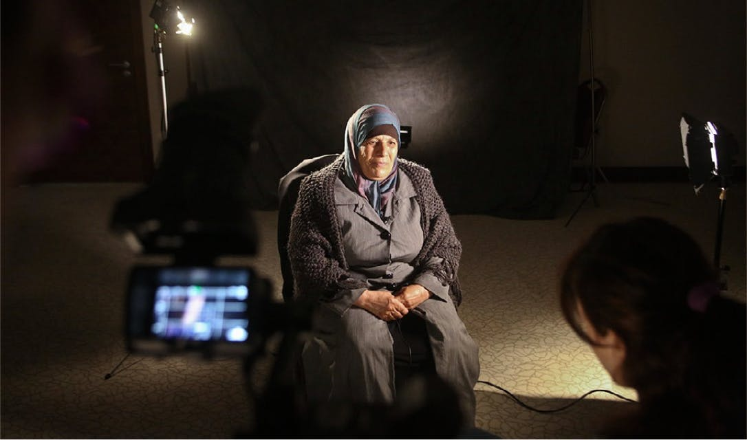 Old woman, on set, being recorded for the documentary.