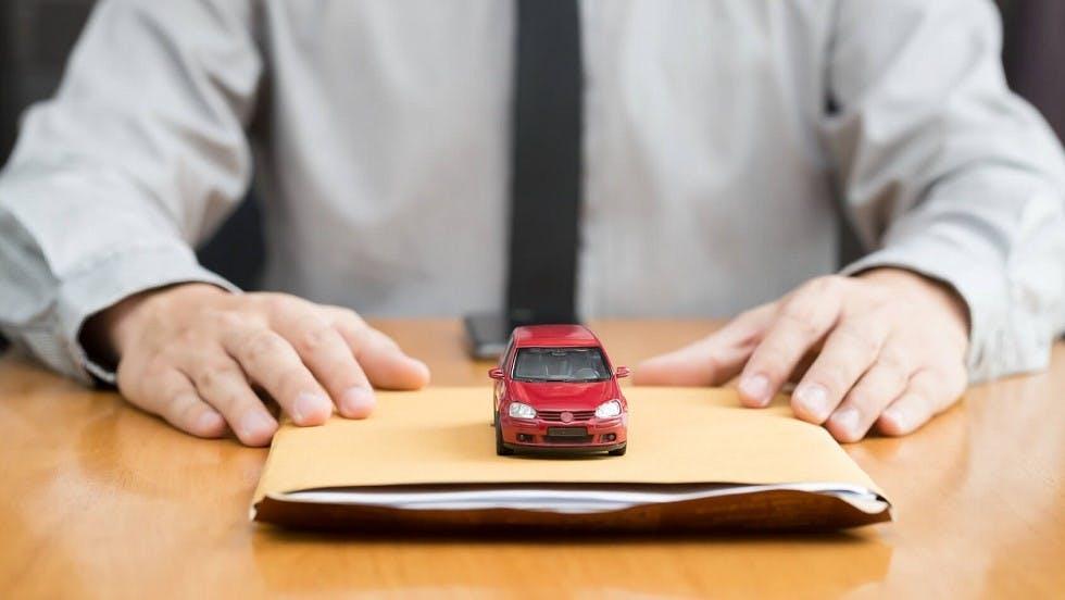 Vendeur remettant a un acheteur les documents lies a sa nouvelle voiture