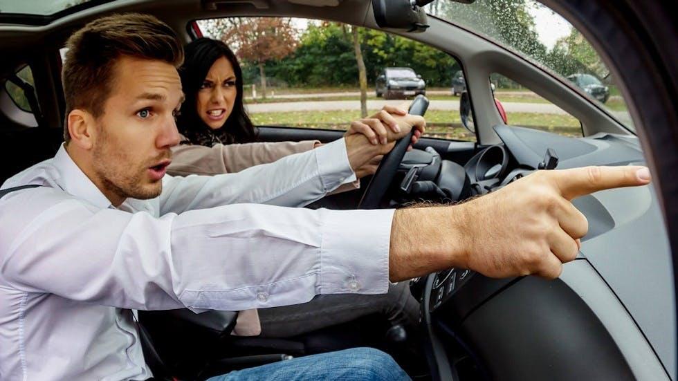 Enseignant de la conduite alertant la candidate sur un risque d'accident imminent