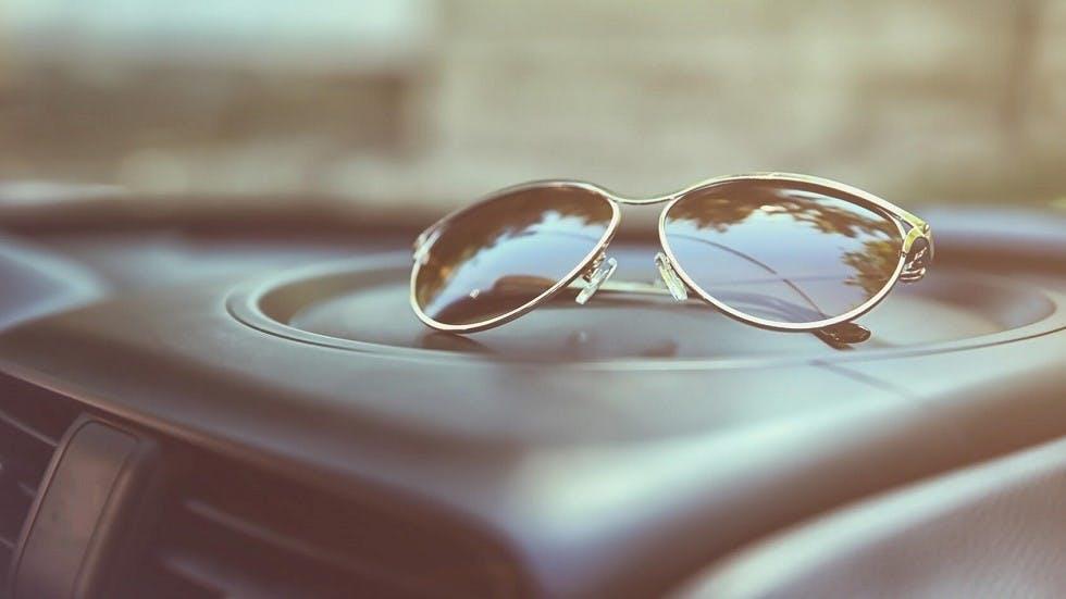 Paire de lunettes de soleil posee sur un tableau de bord d'auto