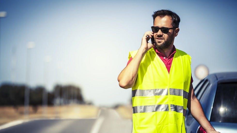 Usager en panne sur une route portant son gilet de haute visibilite