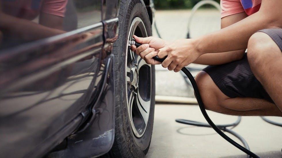 Usager verifiant la pression de ses pneumatiques