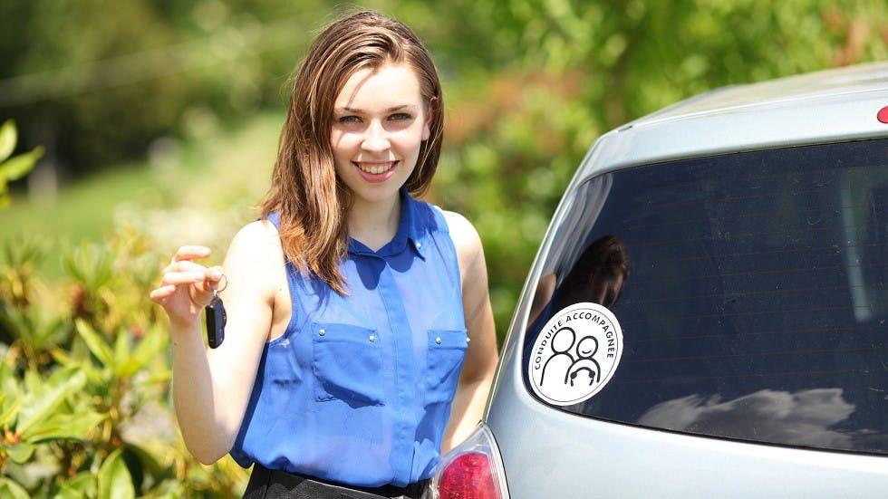 Jeune conductrice presentant ses cles et son macaron de conduite accompagnee