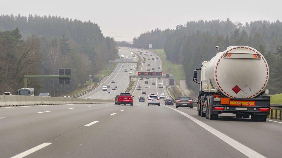 Camion citerne circulant sur une autoroute couverte d'une legere brume