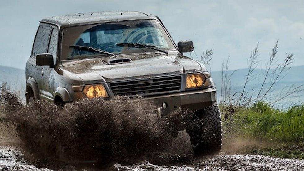 Véhicule tout-terrain roulant dans la boue avec ses feux de croisement allumés