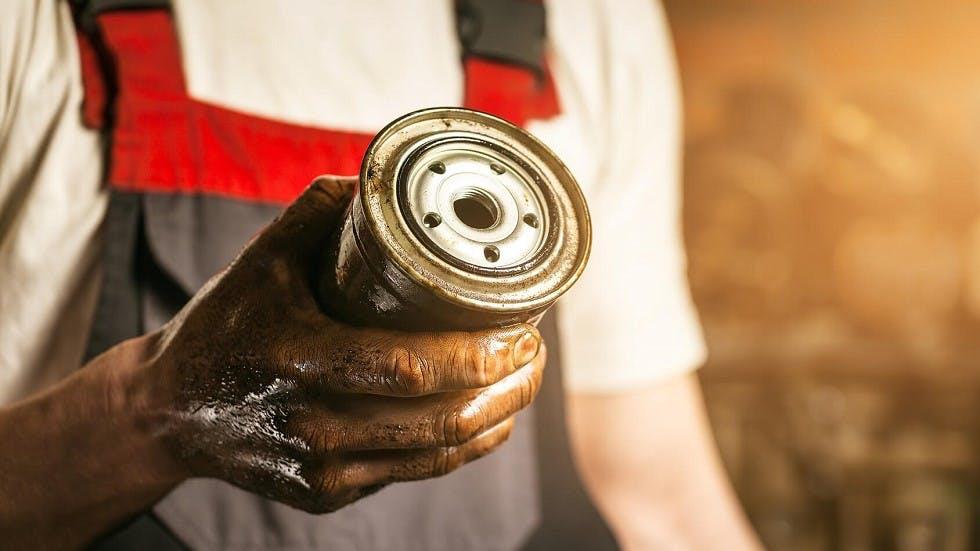 Garagiste tenant un filtre a huile usage