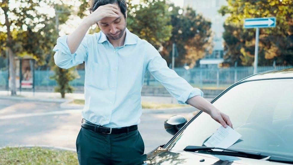 Usager recuperant la contravention sur son pare-brise