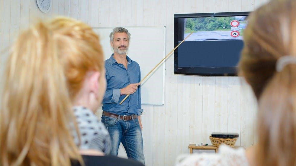 Instructeur presentant les reponses a des questions de l'examen du code de la route