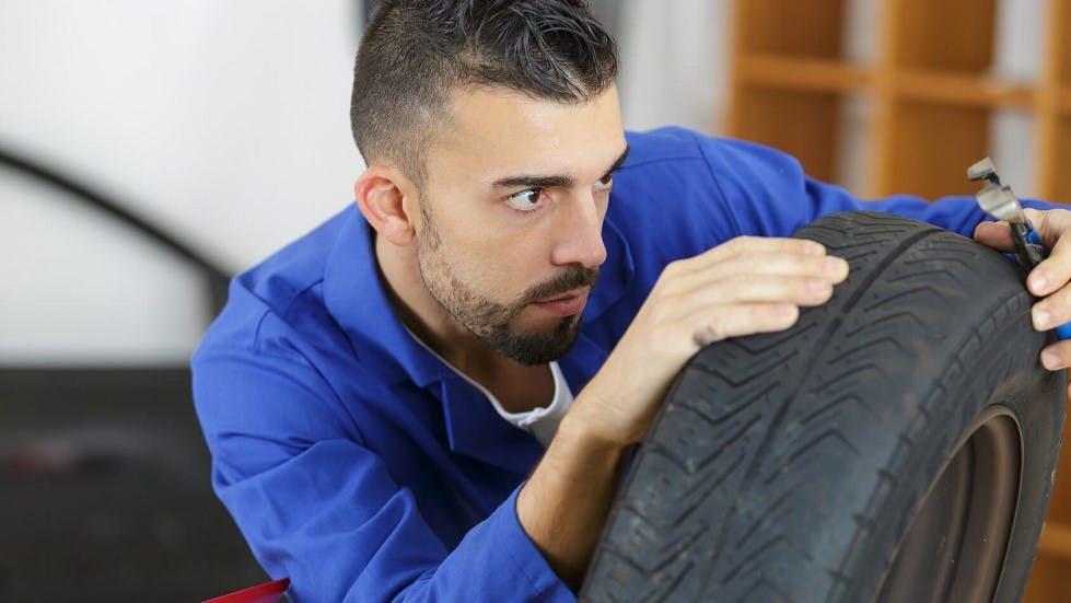 Garagiste verifiant la profondeur des sculptures d'un pneu