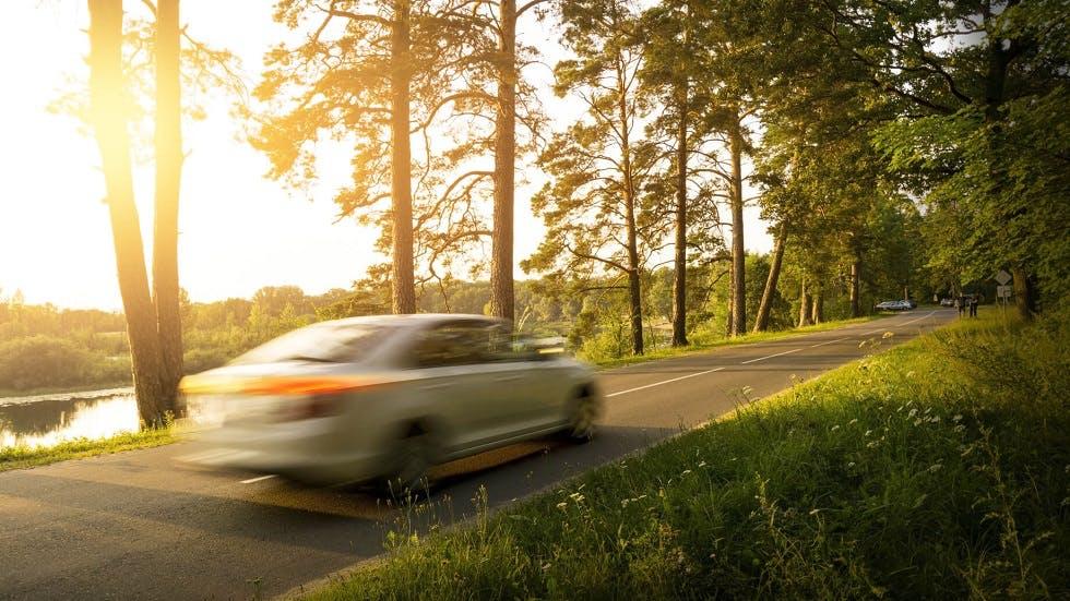 Automobile circulant rapidement sur une route de campagne