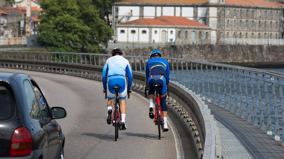 Deux cyclistes circulant devant une auto en agglomeration