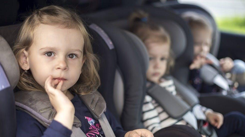 Petites filles installees dans des sieges auto a l'arriere d'une voiture