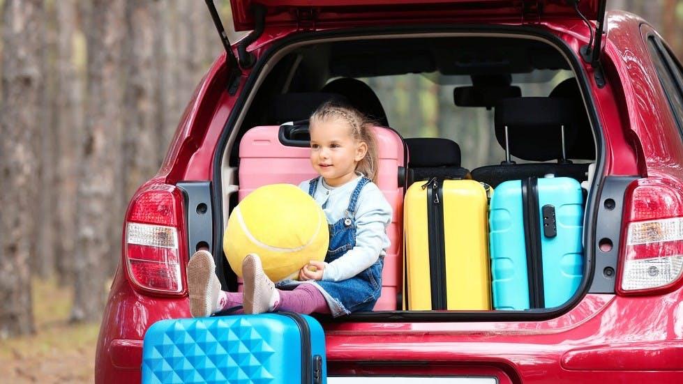 Fillette assise dans un coffre de voiture plein de bagages