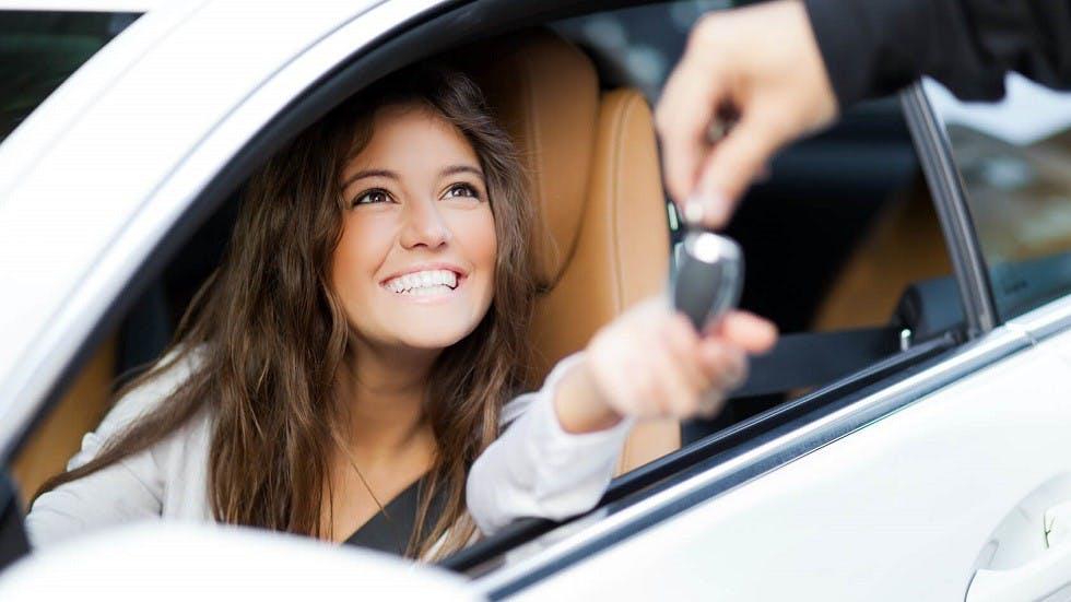 Automobiliste recevant les cles de sa voiture neuve