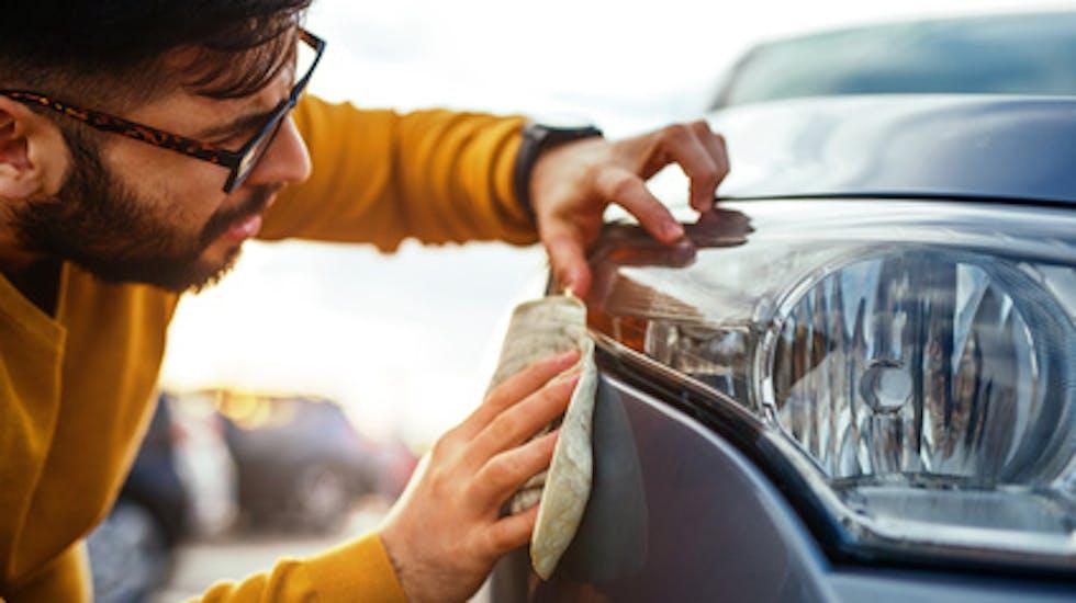 un homme nettoyant la carrosserie de sa voiture
