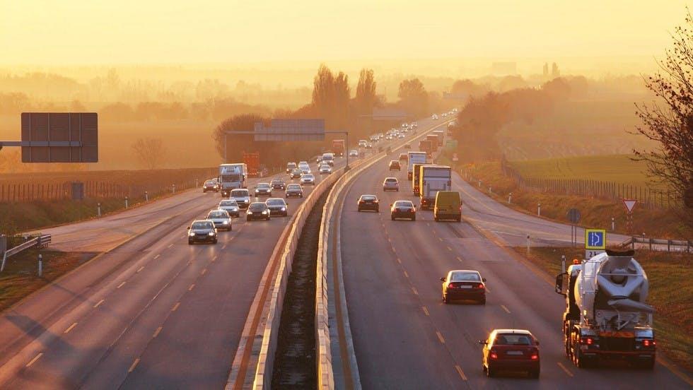 Vehicules roulant sur autoroute sous un coucher de soleil