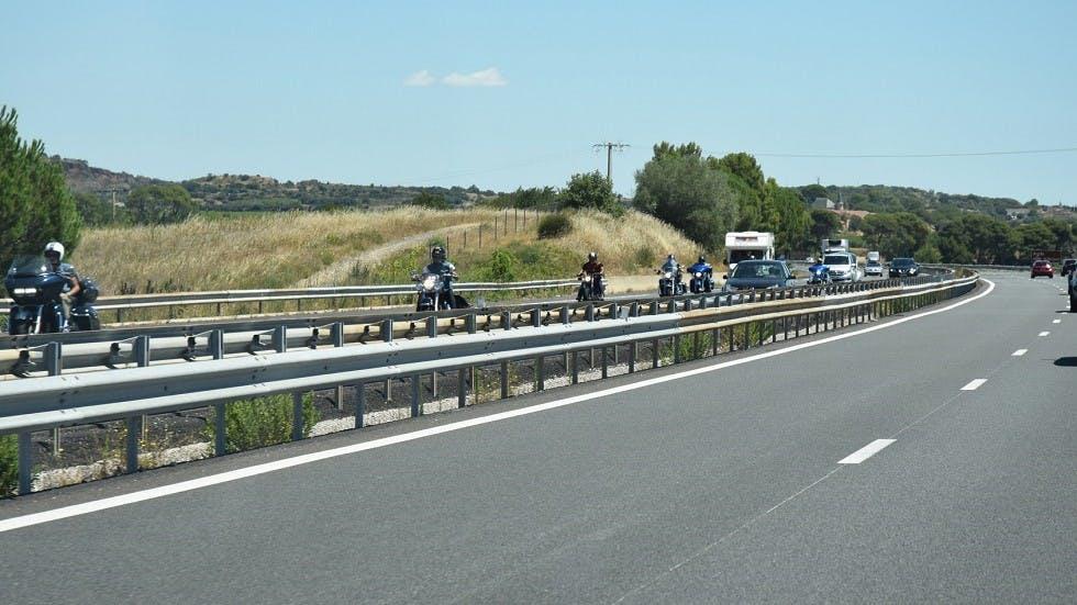 File de deux-roues motorises circulant sur une route