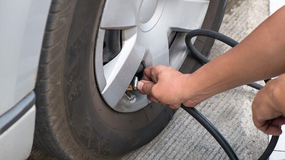Usager de la route gonflant les pneus de son vehicule