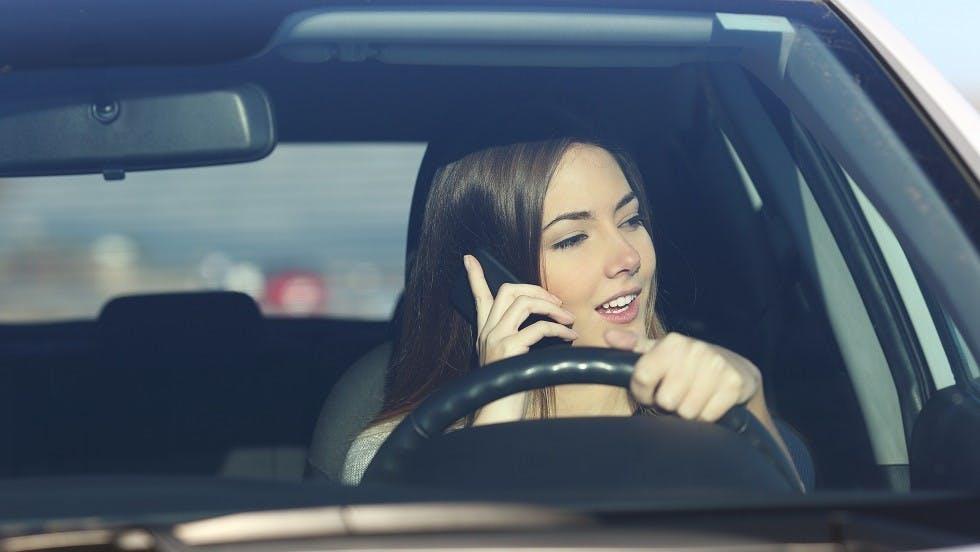 Jeune conductrice telephonant tout en conduisant