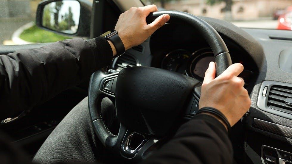 Usager de la route tenant le volant de son vehicule