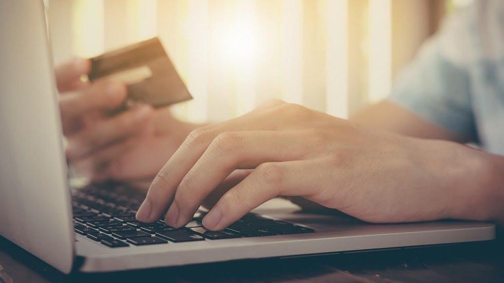 Homme entrant ses coordonnees bancaires sur un site internet