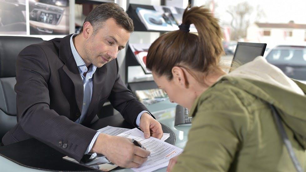 Jeune femme signant un contrat d'assurance auto