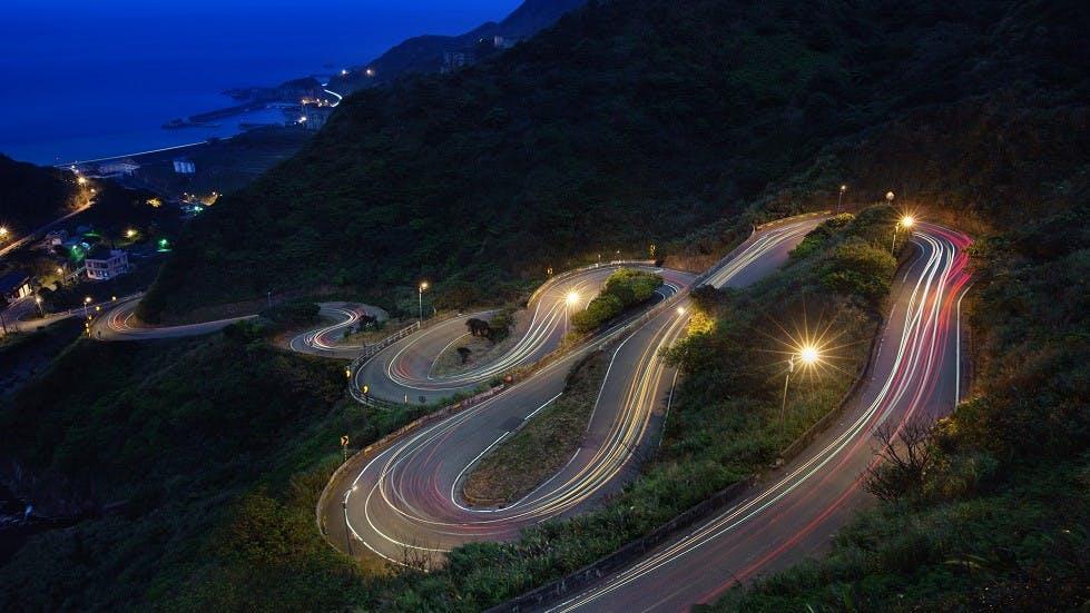 Route de montagne sinueuse illuminee de nuit