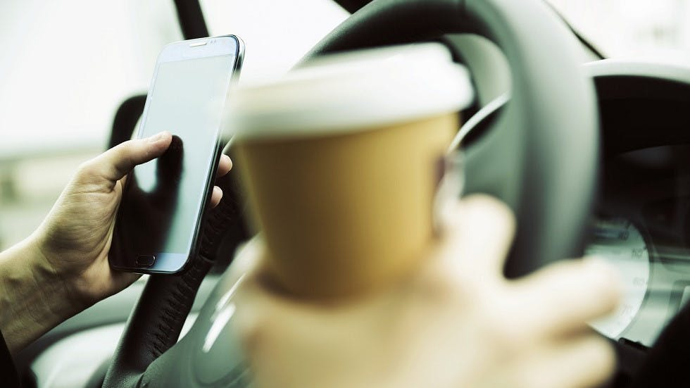 Automobiliste tenant un cafe et un telephone