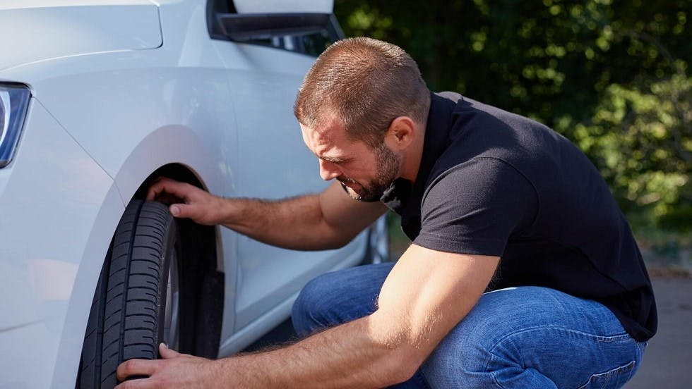 Automobiliste inspectant son pneu creve