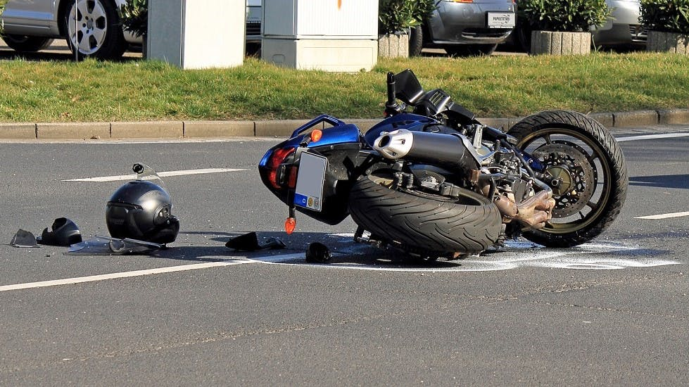 Moto bleue accidentee sur une route