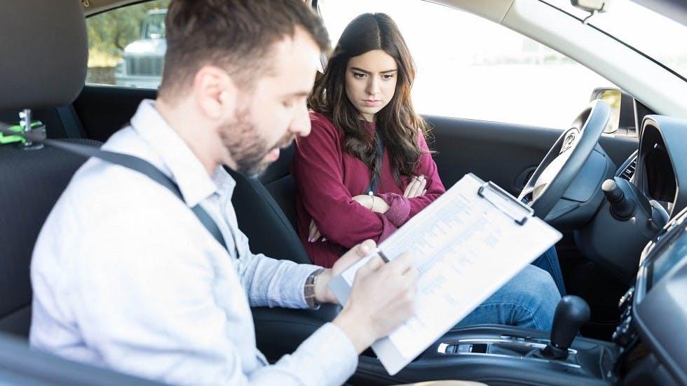 Examinateur du permis de conduire remplissant la grille de notation d'une canddiate
