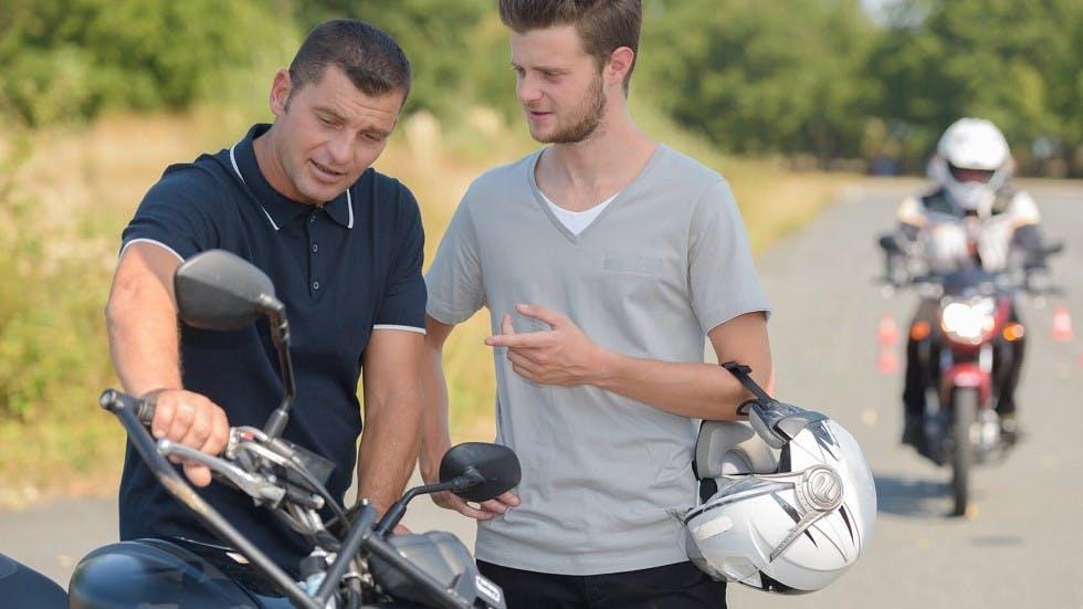 Enseignant de la conduite montrant le fonctionnement d'une moto a un candidat