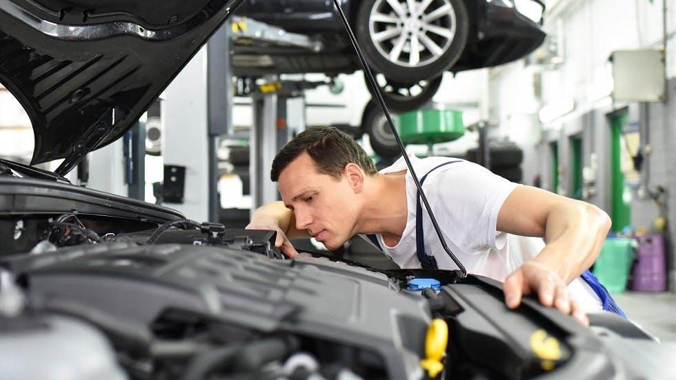 Garagiste controlant l'etat d'un moteur dans le cadre d'un controle technique