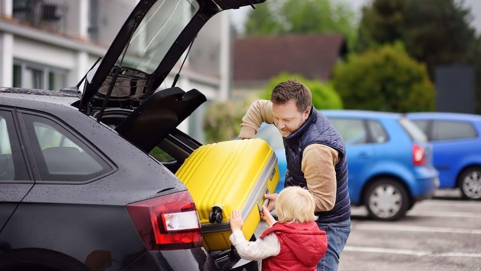 Usager stationné ajoutant des bagages dans son coffre de voiture avec son fils