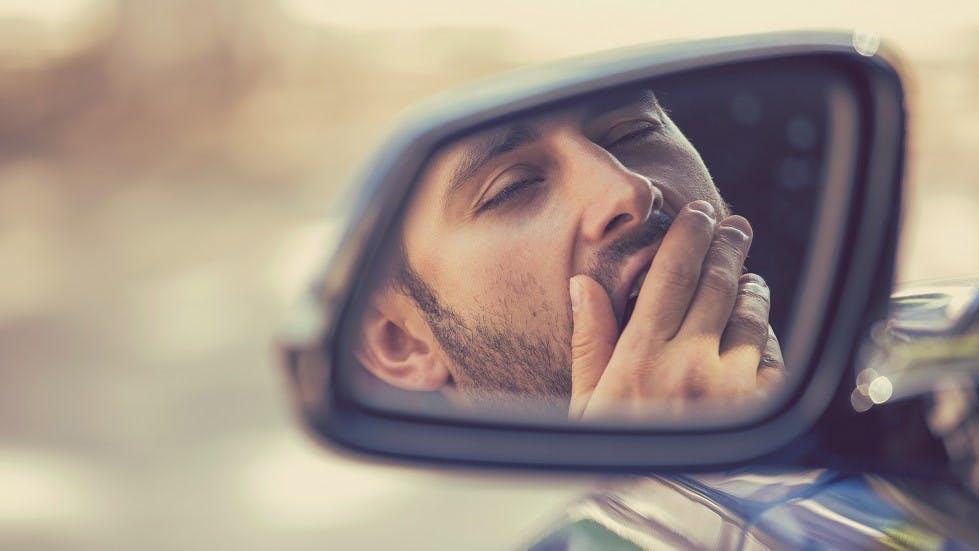 Reflexion d'un usager baillant dans son retroviseur