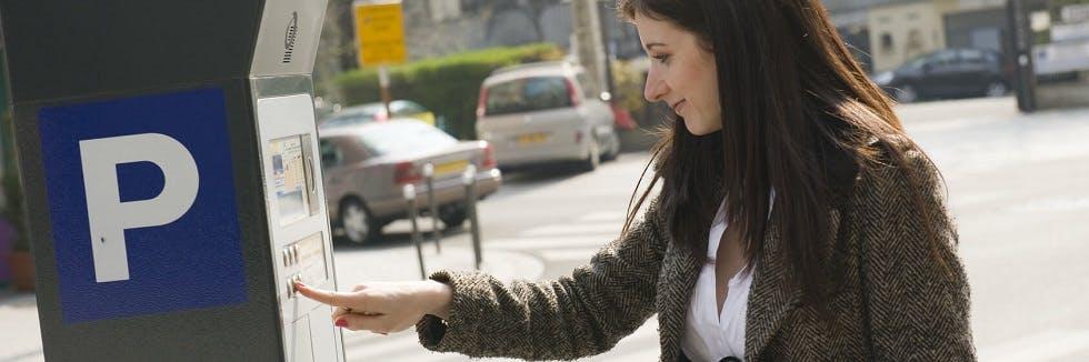 conductrice payant à un horodateur