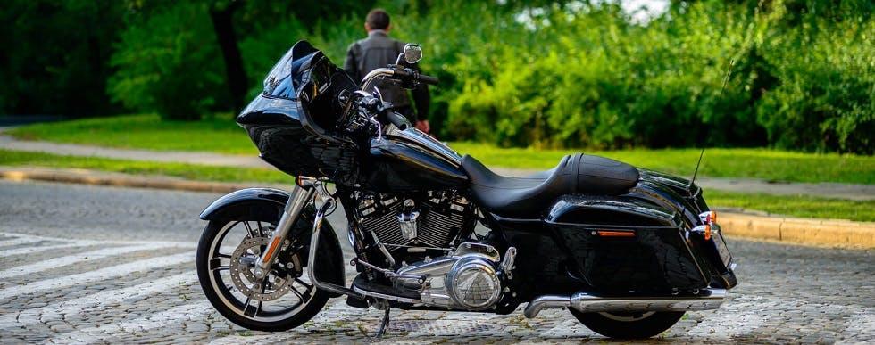 Moto immobile garée le long d'une route pavée