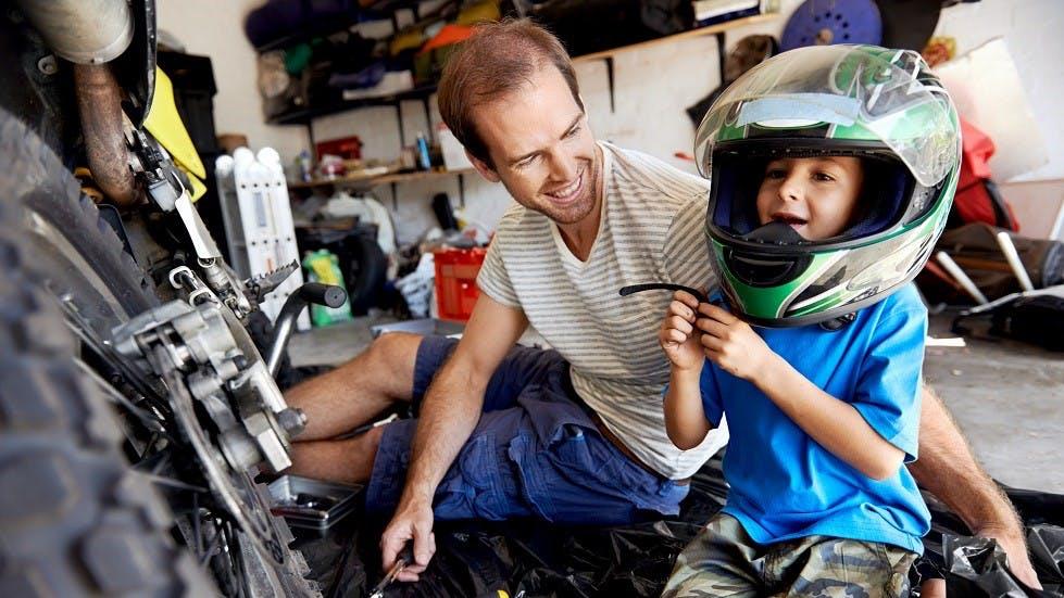 Pere et enfant reparant une moto