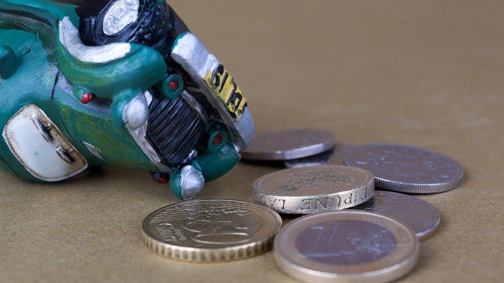 Voiture miniature retournee devant des pieces de monnaie