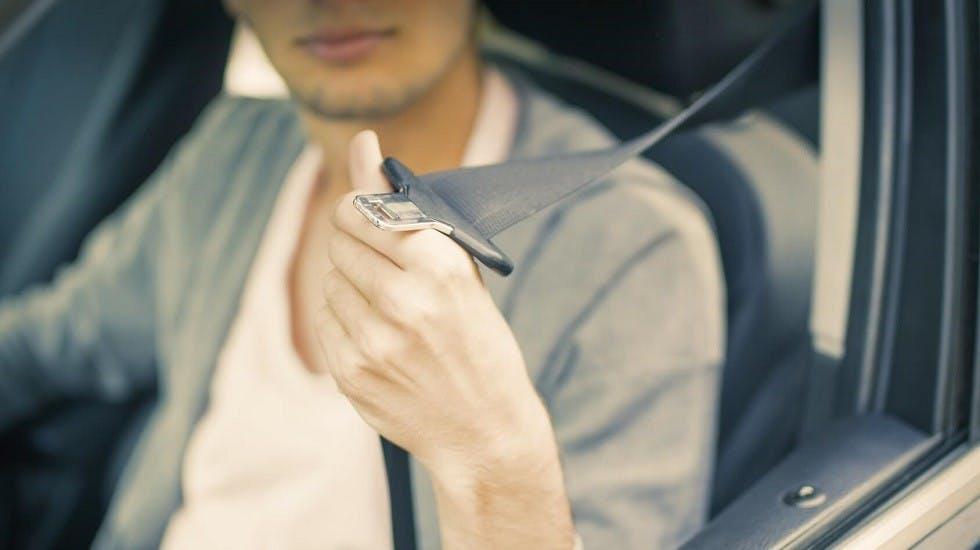 Automobiliste attachant sa ceinture de sécurité