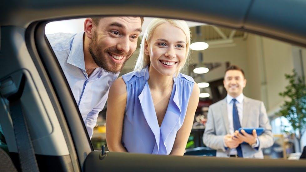 Jeune couple achetant une voiture d'occasion