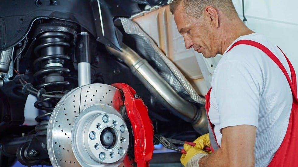 Garagiste travaillant sur l'amortisseur d'une automobile