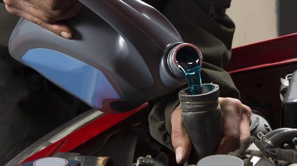 Garagiste versant du liquide de refroidissement dans un moteur