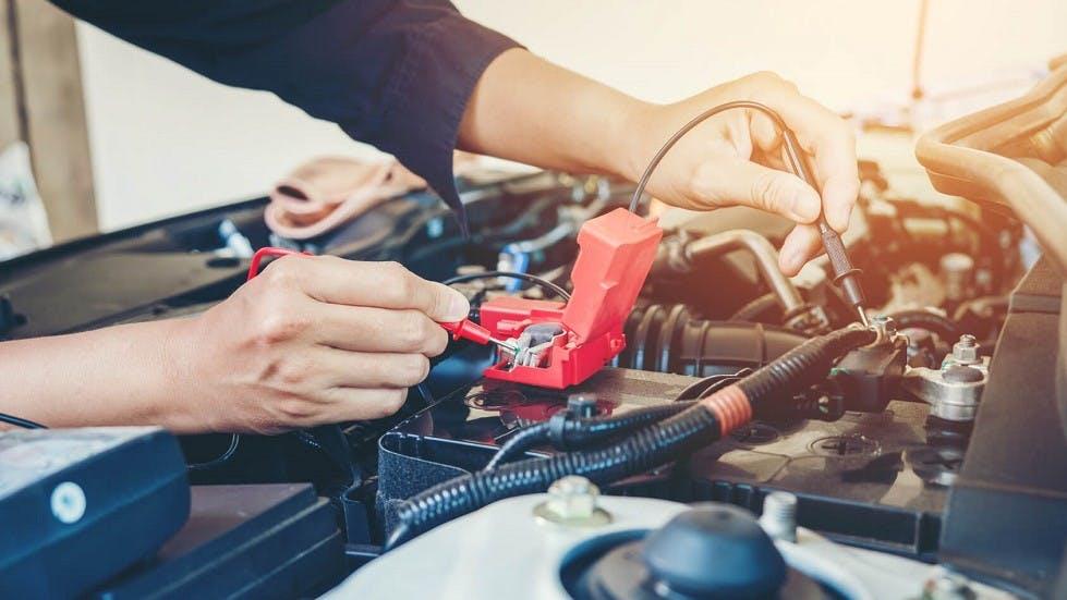 Garagiste travaillant sur la batterie d'une automobile