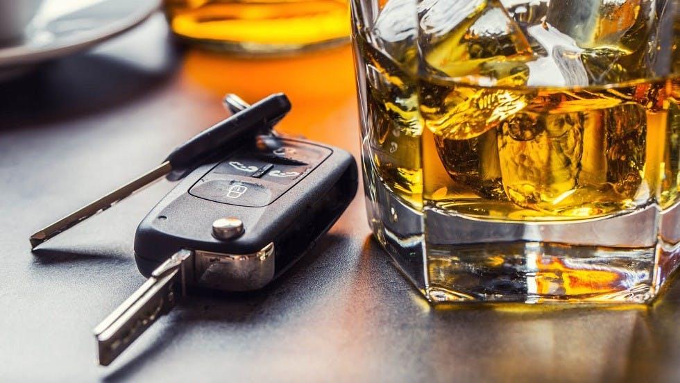 Cles d'une automobile posees pres d'un verre d'alcool
