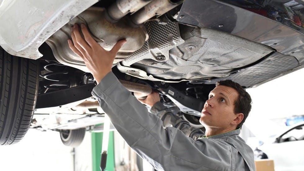 Garagiste travaillant sur le systeme d'echappement d'une voiture