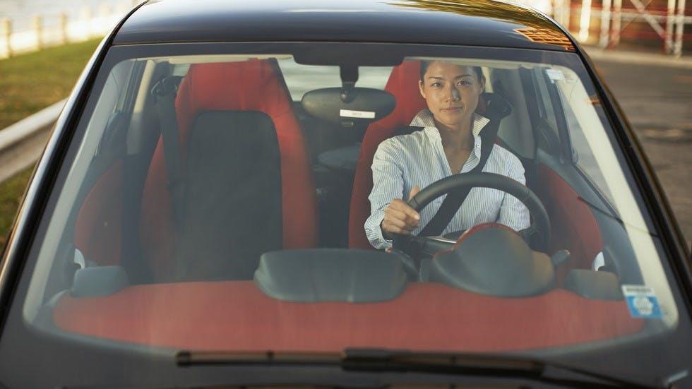 Conductrice circulant au volant d'une voiture sans permis