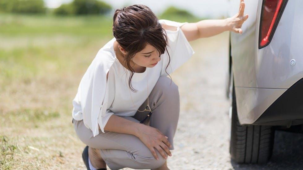 Automobiliste verifiant les pneumatiques de son vehicule
