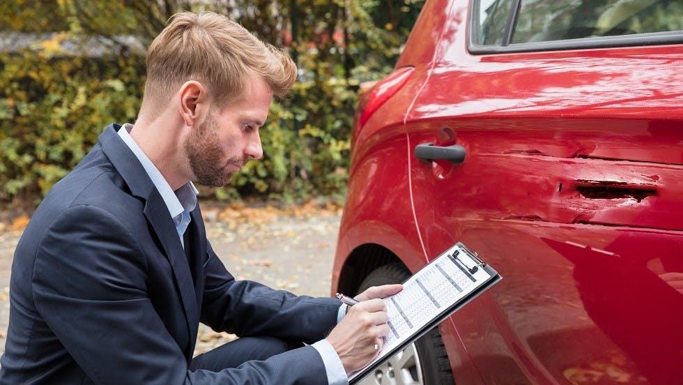 Expert automobile inspectant les degats sur la portier d'un vehicule