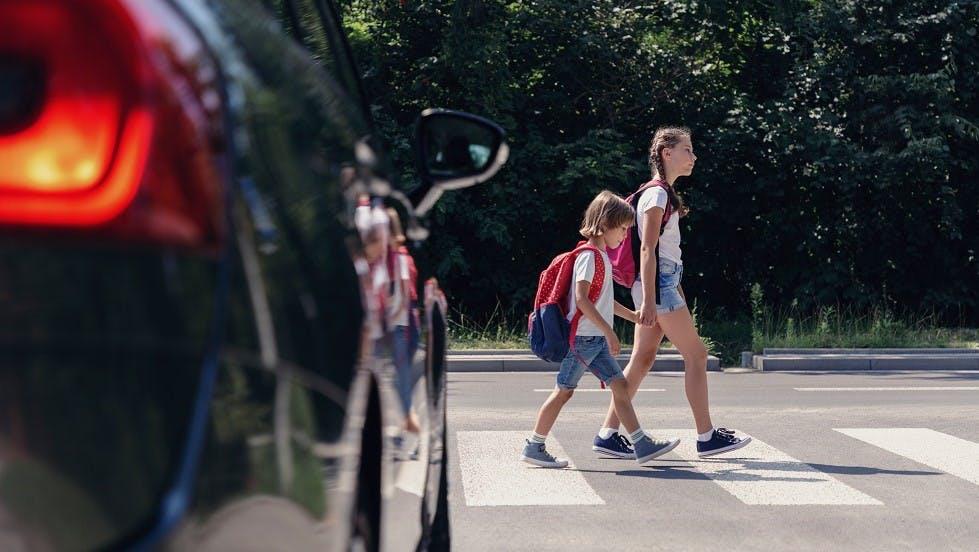 Jeunes enfants traversant une route sur un passage pour pietons
